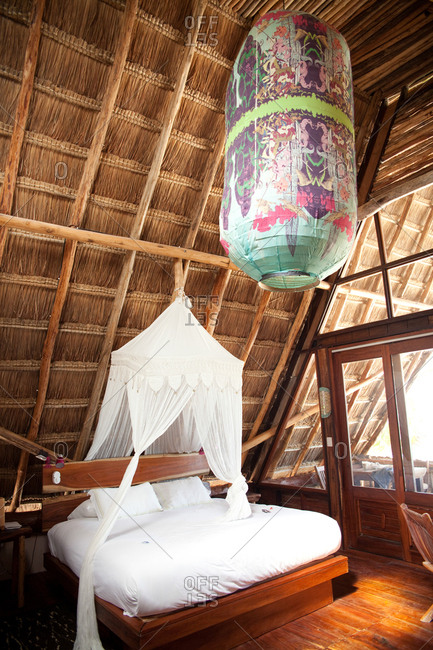 Large paper lantern hanging above a bed in a tropical bedroom