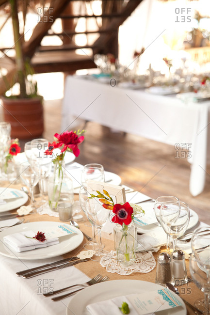 Pink flowers and place settings on elegant reception tables