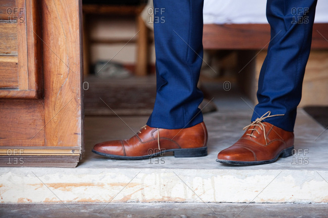 Man in brown leather loafers and blue pants in a doorway