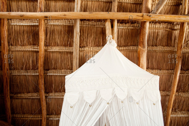 White canopy hanging from an angled thatch roof