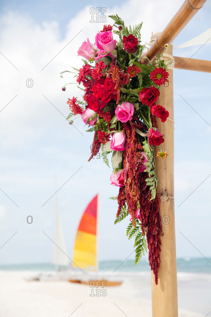 Floral arrangement with red and pink roses hanging from a wooden frame on a beach