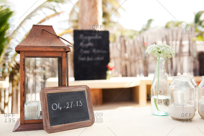 Slate chalkboard leaning against a lantern with a wedding date on it