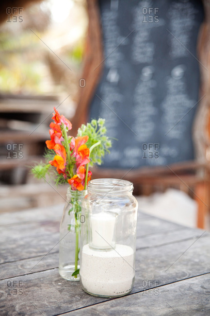 Orange flowers, sand and candles in jars on a table