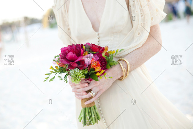 Bride on a beach holding a bouquet of pink, orange and green flowers
