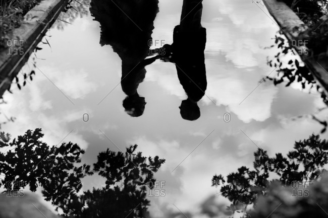 Reflection of a newlywed couple holding hands in a still pool
