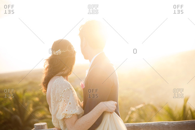 Newlywed couple embracing on a deck at sunset