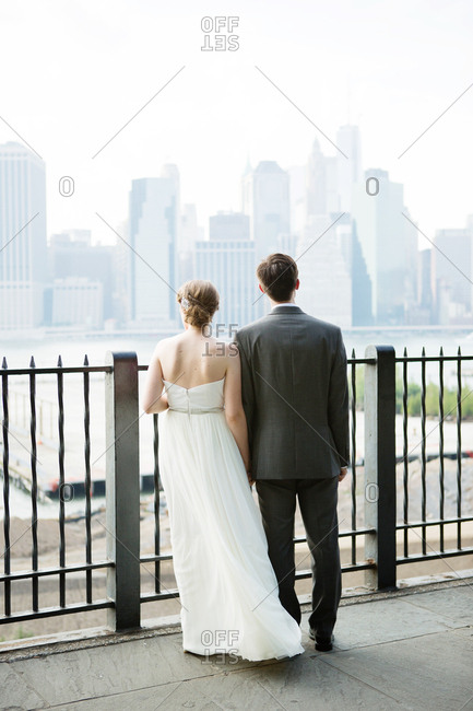 Bride and groom standing at a railing looking at a city skyline