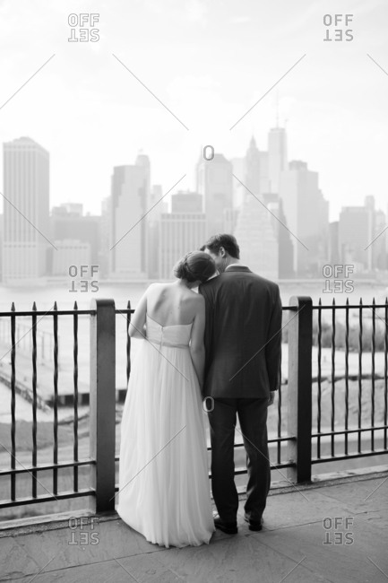 Newlywed couple standing at a railing looking at a city skyline