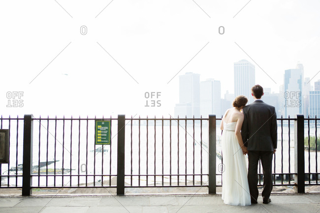 Newlywed couple looking at a city skyline in the fog