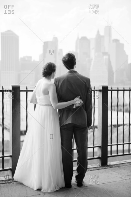 Newlywed couple holding hands and looking at a city skyline in fog