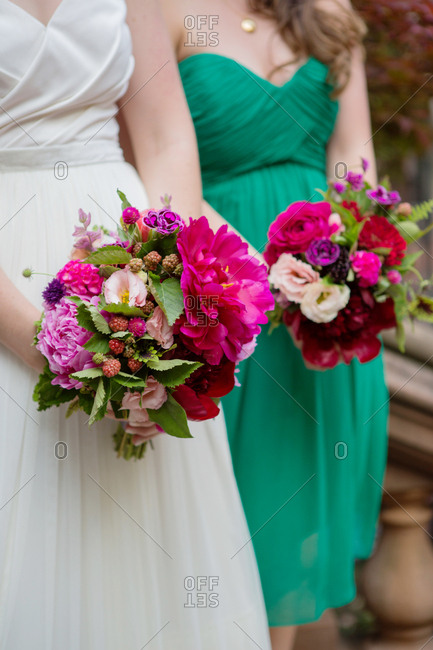 Bride and bridesmaid holding bouquets of pink and purple flowers