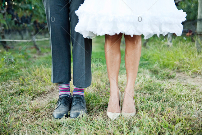 Feet of a bride and groom standing in a field