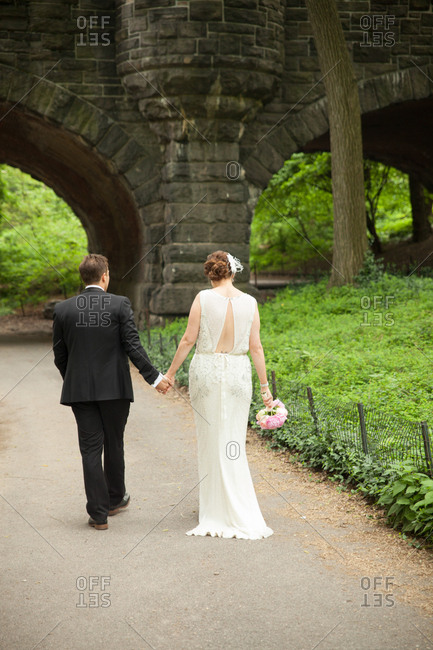 Newlywed couple walking together and walking in Central Park