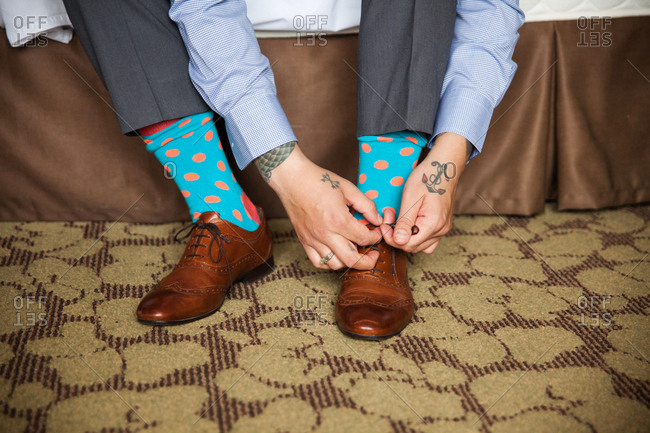 Hands of a man with polka dot socks tying brown leather loafers
