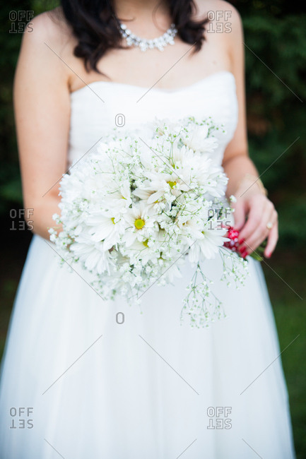 Bride in a white gown holding a bouquet of daisies
