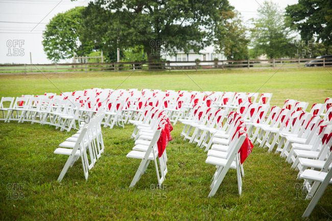 Curved rows of white chairs with red bandanas in a field for a wedding