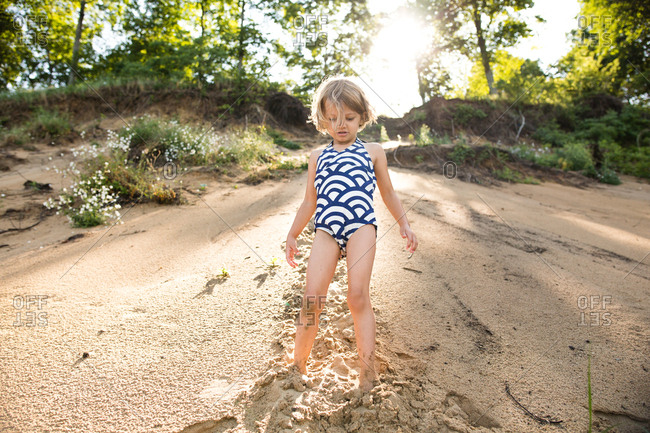 Little girl in a swimsuit standing in wet sand on a lake shore