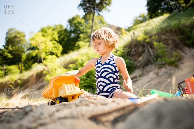 Little girl playing with a toy dump truck on a beach
