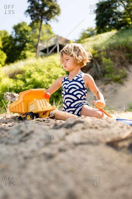 Little girl playing on a lakeshore with a plastic dump truck