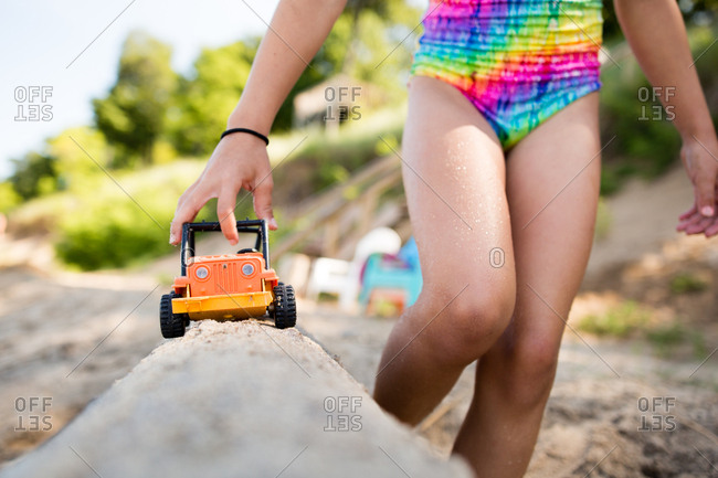 Little girl pushing a toy truck along sand on a beach