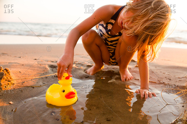 Little girl playing with rubber ducks on a beach at sunset