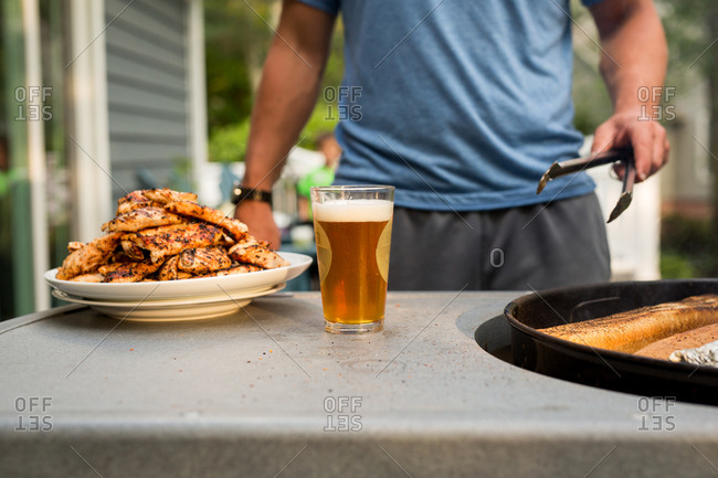 Man standing on a deck preparing chicken on a grill