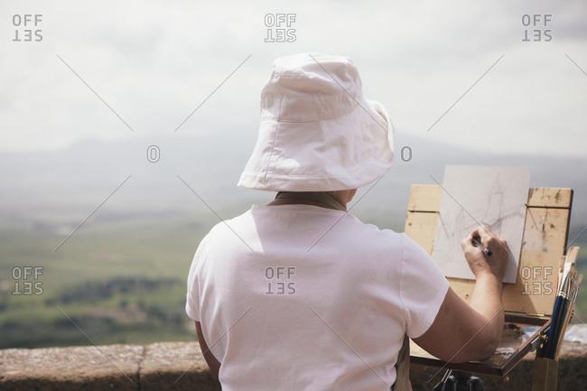 Woman painting a landscape