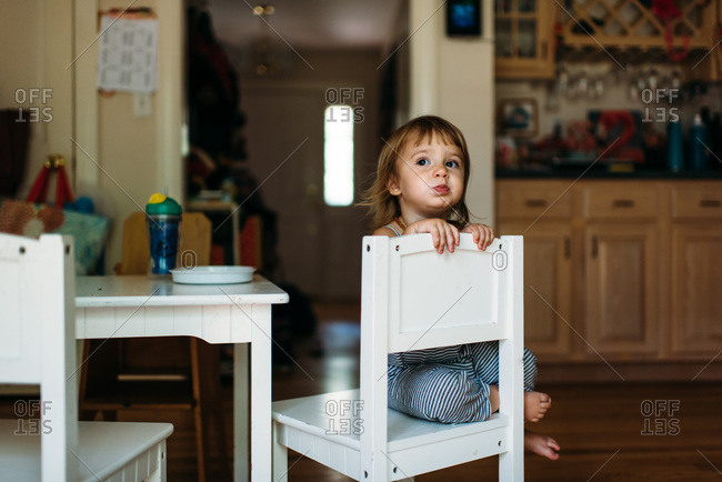 Toddler sitting backwards in a chair in a kitchen while eating.
