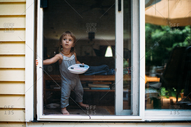 Toddler girl opening screen door to go outside.