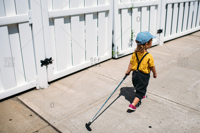 Toddler wearing overalls dragging golf club outside.