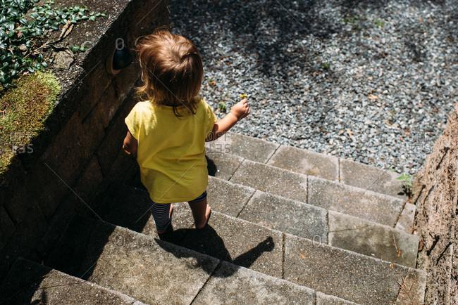 Toddler girl walking down steps outside holding a dandelion flower.