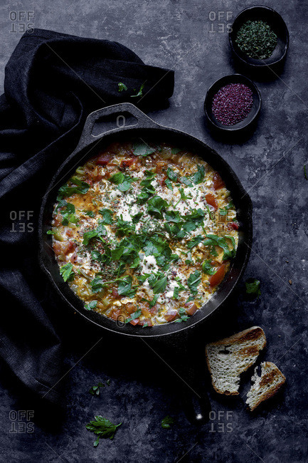 Shakshuka a dish of eggs poached in a sauce of tomatoes, chili peppers, and onions, spiced with cumin.
