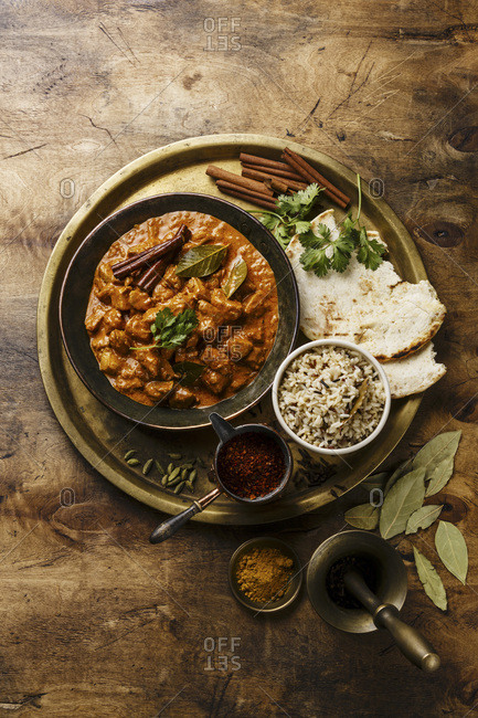 Chicken tikka masala in a copper pan with rice and naan bread on wooden background