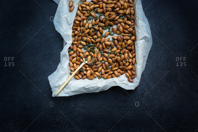 Roasted pumpkin seeds and almonds on parchment paper