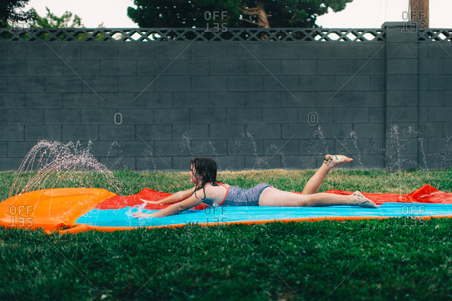 Young girl playing on backyard water slide