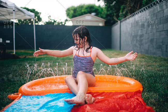 Young girl sitting in pool of water on backyard water slide