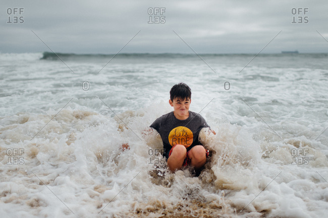 Boy sitting in the ocean waves