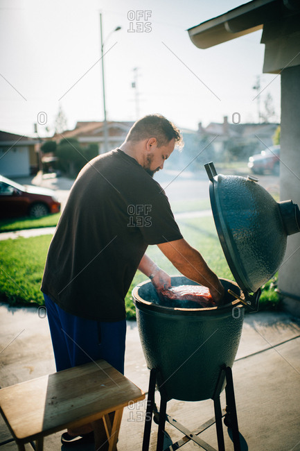 Man grilling meat on a grill in his driveway