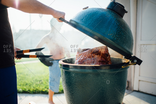 Man with tongs barbecuing meat in grill