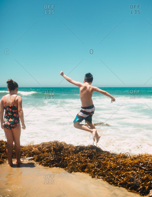 Kids on beach jumping over washed up seaweed