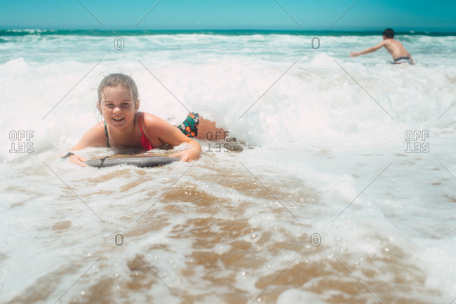 Girl playing in ocean waves with brother in background