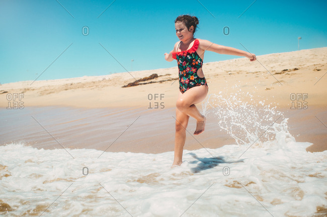 Girl running into the ocean waves