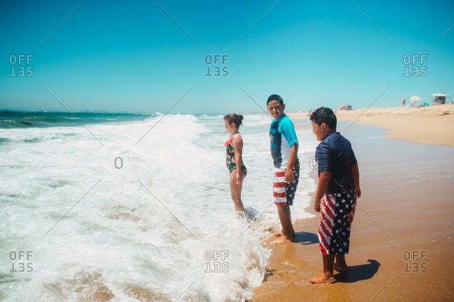 Three kids standing on coastline as waves crash into them