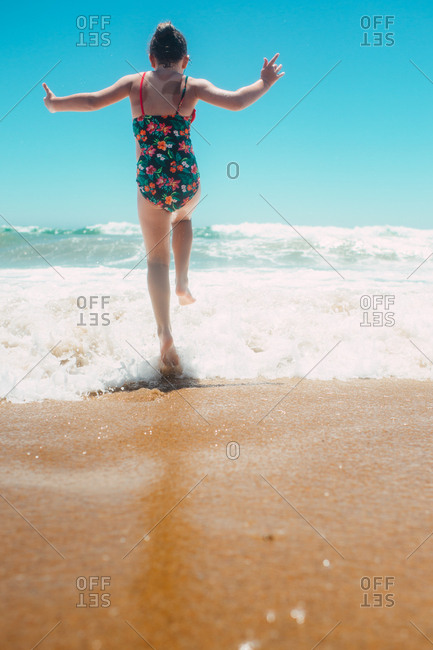 Back view of girl running into the ocean waves