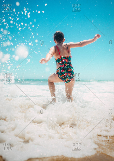 Rear view of girl running into the ocean waves
