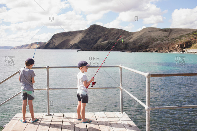 Two boys fishing off dock