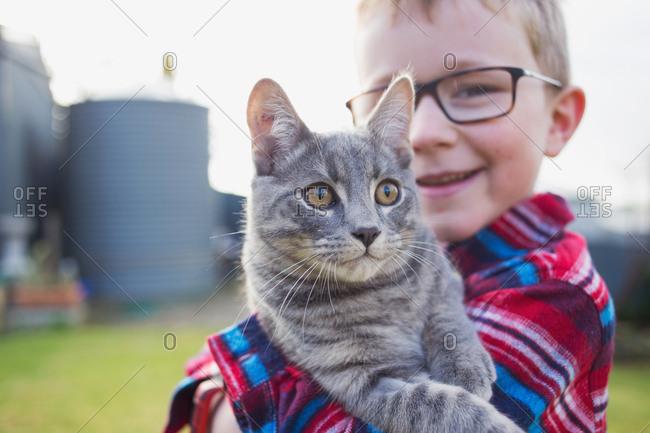 Boy holding gray kitten