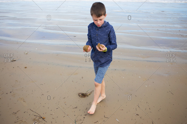 Young boy collecting sea sponge on the ocean shore