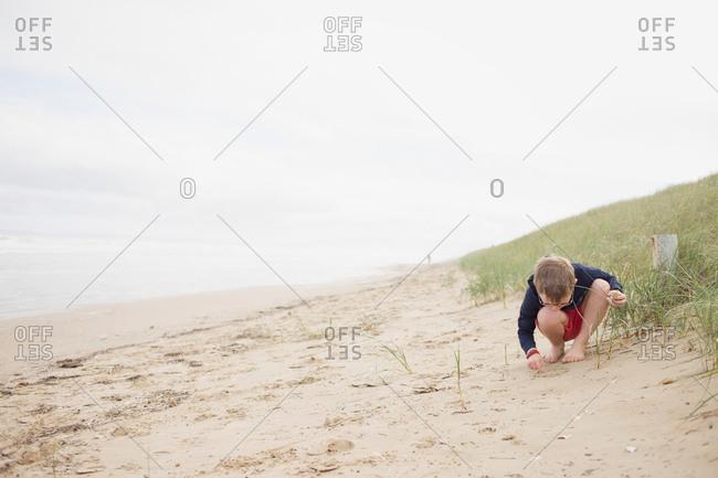 Little boy drawing in sand on beach
