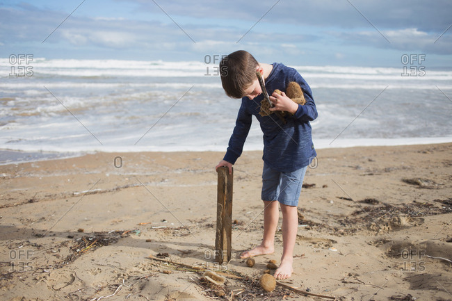 Young boy collecting sea sponge and drift wood on the ocean shore